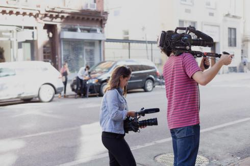People with cameras shooting a documentary on the street