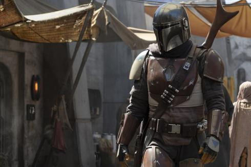 A still from the TV series The Mandalorian, showing the main character in a market.
