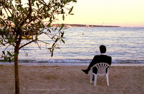 Man sitting on the beach in a tux at the Cannes Film Festival